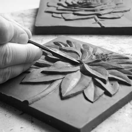 The master relief is carved in clay. From this a master mould is made.
